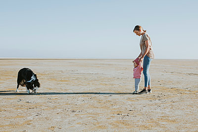 Netherlands, Schiermonnikoog, mother walking with little daughter on the beach at low tide - p300m1228755 by Daniel Weisser