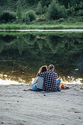 Romantic couple sitting at the riverside - p300m2043135 von Vasily Pindyurin
