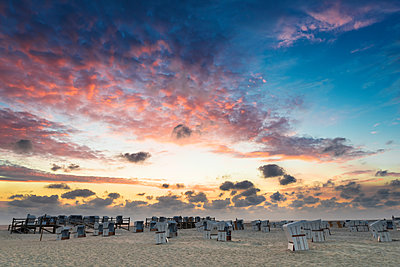 Germany, Sankt Peter Ording, hooded beach chairs on the beach in sunset - p300m2104134 by Markus Kapferer