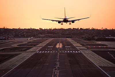 A plane landing at sunset.  - p343m1168180 by Rob Hammer