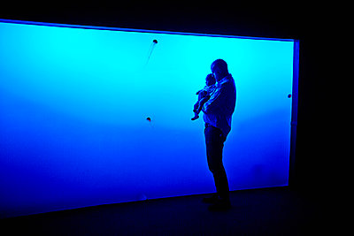 Father and son watching jellyfish at aquarium - p429m802508 by Cultura