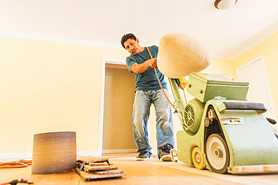 Hispanic man refinishing floors in new house - p555m1408524 by Sollina Images