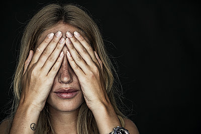 Woman holding hands over eyes - p623m1495154 by Frederic Cirou