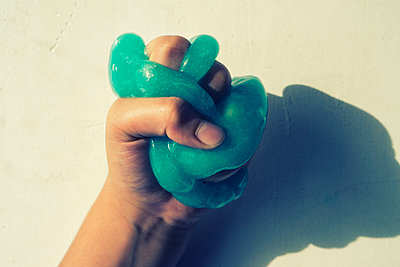 Close up of a hand squeezing slime  - p794m2057310 by Mohamad Itani