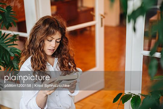 Junge Frau liest ein Buch - p586m1200158 von Kniel Synnatzschke