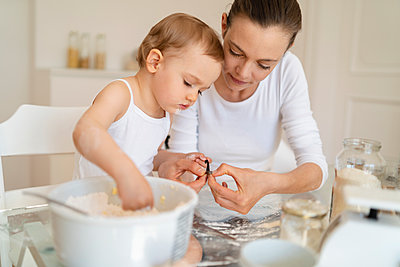 Mother and little daughter making a cake together in kitchen at home - p300m2102598 von Daniel Ingold