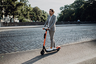 Businessman with e-scooter in the city - p300m2140539 by Johanna Lohr