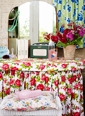 Floral patterned dressing table and mirror with cut flowers in Isle of Wight home;  UK - p349m920075 by Rachel Whiting