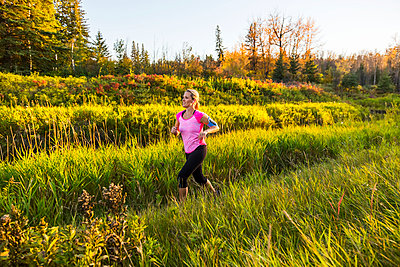 An attractive middle-aged woman wearing active wear and listening to music while running along a creek in a city park at sunset on a warm autumn evening; Edmonton, Alberta, Canada - p442m2019658 by LJM Photo