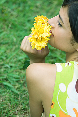Young woman smelling flowers - p6242278f by Milena Boniek