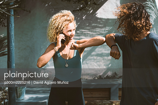 Smiling woman giving elbow bump to man while talking on mobile phone outdoors - p300m2225216 by David Agüero Muñoz