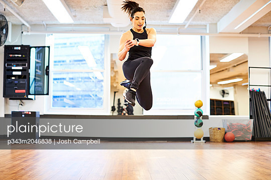 Fitness instructor demonstrating jump move - p343m2046838 by Josh Campbell