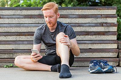 Jogger benutzt Smartphone nach Training. - p1396m1463549 von Hartmann + Beese