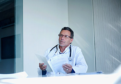 Thoughtful male doctor with medical report contemplating while sitting in hospital - p300m2281417 by LOUIS CHRISTIAN