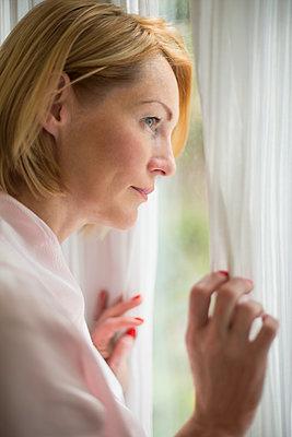 Thoughtful woman wearing bathrobe looking through window in bathroom - p301m1482441 by Vladimir Godnik