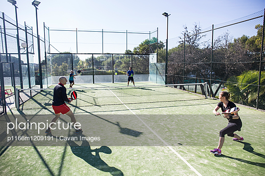 Friends playing tennis in court against sky