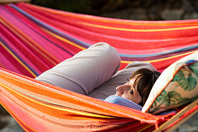 young woman lying in hammock at sunset - p1166m2269374 by Cavan Images