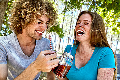 Laughing young couple having a drink in forest - p300m1535707 by Martina Ferrari