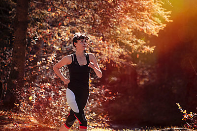 Woman jogging in autumn forest - p300m2166779 by Studio 27