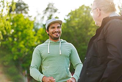 Men talking outside - p312m2237124 by Phia Bergdahl