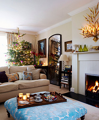 Christmas tree and distressed mirror with wooden tray on ottoman at fireside - p349m790267 by Brent Darby
