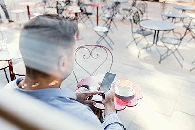 Businessman using smart phone at sidewalk cafe seen through glass window - p426m1196704 by Maskot