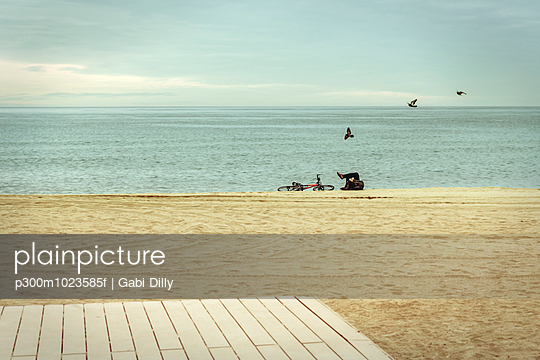 Spain, Barcelona, person relaxing on the beach - p300m1023585f by Gabi Dilly