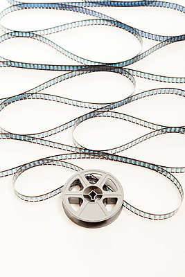 An old plastic cine film reel with film uncoiling unwinding from it  - p1302m1148572 by Richard Nixon