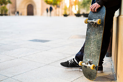 Young man with skateboard leaning against house front - p300m1356031 by Kike Arnaiz