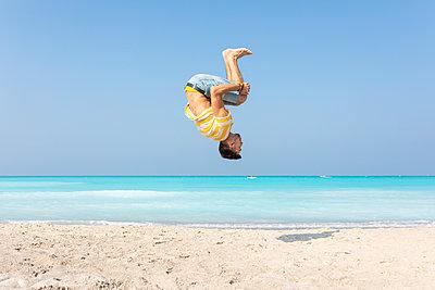 Young man doing a somersault on the beach - p300m2059538 von William Perugini