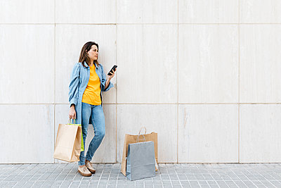 Young brunette woman using smartphone after shopping - p300m2143851 by Josep Rovirosa
