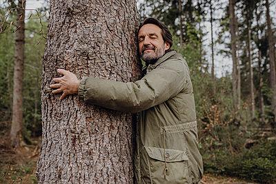 Mature hiker hugging tree trunk - p300m2198842 by Johanna Lohr