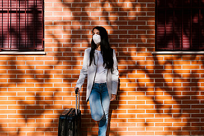Woman with suitcase standing against brick wall - p300m2240727 by Ezequiel Giménez
