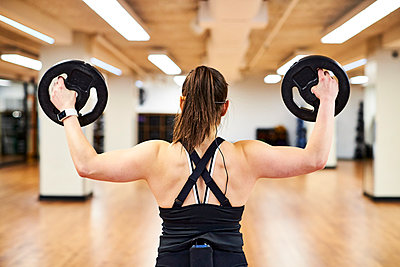 Woman holding weights at gym - p343m2046836 by Josh Campbell