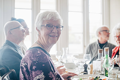 Portrait of senior woman smiling while sitting by friends in restaurant - p426m2149121 by Maskot