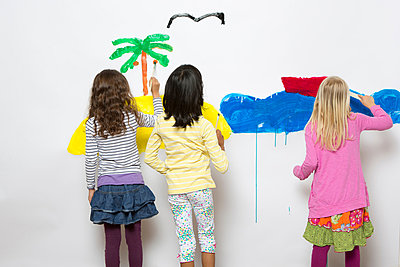 Three girls painting ocean and island on wall - p429m819919f by Severin Schweiger