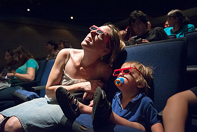 Mother and toddler son watching 3-D movie in theater - p624m1174339 by Jerome Gorin