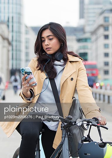Woman on bicycle using smart phone in city - p1023m2208376 by Paul Bradbury