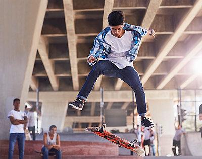 Friends watching teenage boy flipping skateboard at skate park - p1023m1172794 by Trevor Adeline