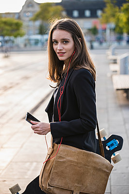 Young woman with longboard and cell phone in the city on the move - p300m2059604 by Uwe Umstätter