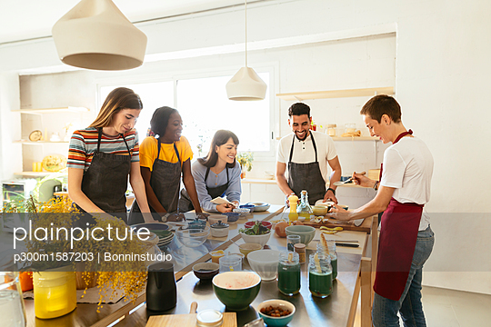 Friends and instructor in a cooking workshop preparing food - p300m1587203 von Bonninstudio