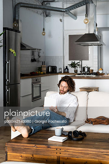 Relaxed man sitting on couch at home using tablet - p300m2143980 by Giorgio Fochesato