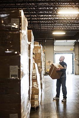 Caucasian male  warehouse worker checking inventory on stacks of cardboard boxes holding products in a large distribution warehouse with loading dock door in the background. - p1100m1575479 by Mint Images