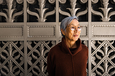 Smiling Senior Woman looking away against ornate city gate background - p1166m2285621 by Cavan Images