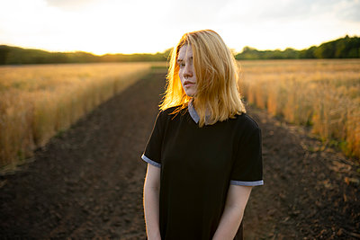 Young woman stands on farm track between cornfields - p1646m2229926 by Slava Chistyakov