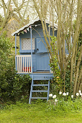 A painted wooden summer play house in the garden - p349m790651 by Polly Eltes