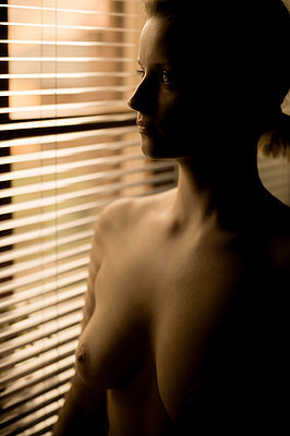 Young woman with bare chest at the window - p552m2248550 by Leander Hopf