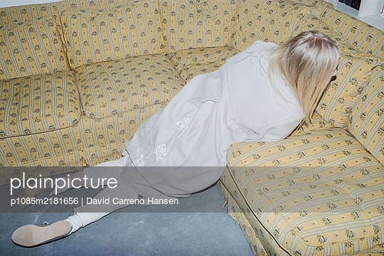 Freaked out blonde woman in front of sofa - p1085m2181656 by David Carreno Hansen