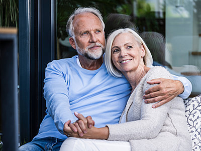 Mature couple holding hands while sitting at balcony - p300m2293818 by Uwe Umstätter