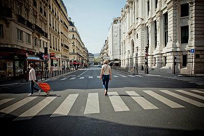 Two women walking in an empty avenue - p445m2176737 by Marie Docher